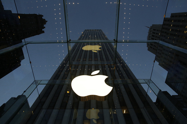 FILE - In this Wednesday, Nov. 20, 2013, file photo, the Apple logo is illuminated in the entrance to the Fifth Avenue Apple store, in New York. Apple Inc. reports quarterly financial results after the market closes Monday, Jan 27, 2014. (AP Photo/Mark Lennihan, File)